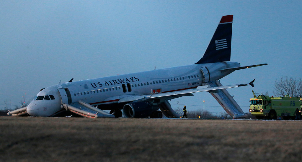 . A damaged US Airways jet lies at the end of a runway at the Philadelphia International Airport, Thursday, March 13, 2014, in Philadelphia. Airline officials said the flight was heading to Fort Lauderdale, Fla., when the pilot was forced to abort takeoff around 6:30 p.m., after the front landing gear failed. An airport spokeswoman said no injuries have been reported. (AP Photo/Matt Slocum)