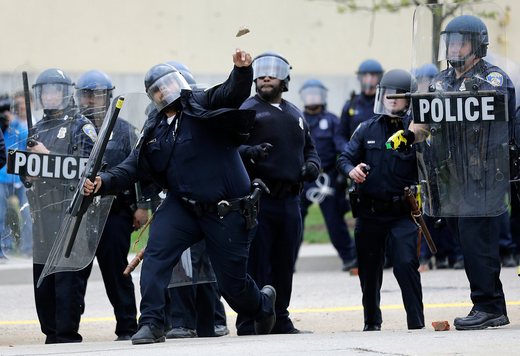 . A police officer throws an object at protestors, Monday, April 27, 2015, following the funeral of Freddie Gray in Baltimore. Gray died from spinal injuries about a week after he was arrested and transported in a Baltimore Police Department van. (AP Photo/Patrick Semansky)
