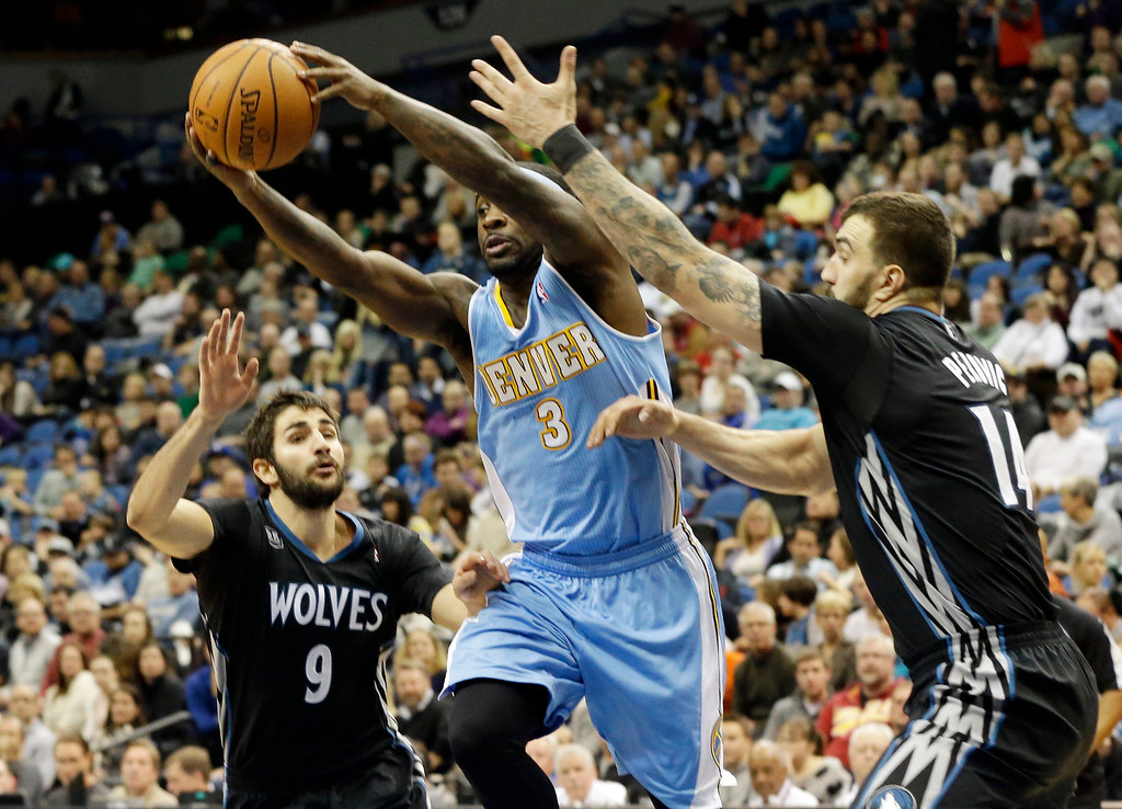 . Denver Nuggets\' Ty Lawson, center, squeezes between Minnesota Timberwolves\' Ricky Rubio, left, of Spain, and Nikola Pekovic of Montenegro, in the second half of an NBA basketball game, Wednesday, Nov. 27, 2013, in Minneapolis. Lawson led the Nuggets with 23 points in the Nuggets\' 117-110 win. (AP Photo/Jim Mone)