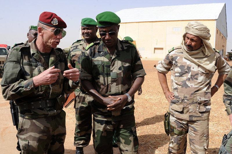 . Niger army chief of staff Seini Garba (C), flanked by Mali\'s army colonel Alaji Ag Gamou (R), listens to French Colonel Zavier (L) on February 2, 2013 in Gao. French President Francois Hollande received a rapturous welcome as he visited Mali to push for African troops to take over a French-led offensive that drove back Islamist rebels from the country\'s desert north.  SIA KAMBOU/AFP/Getty Images