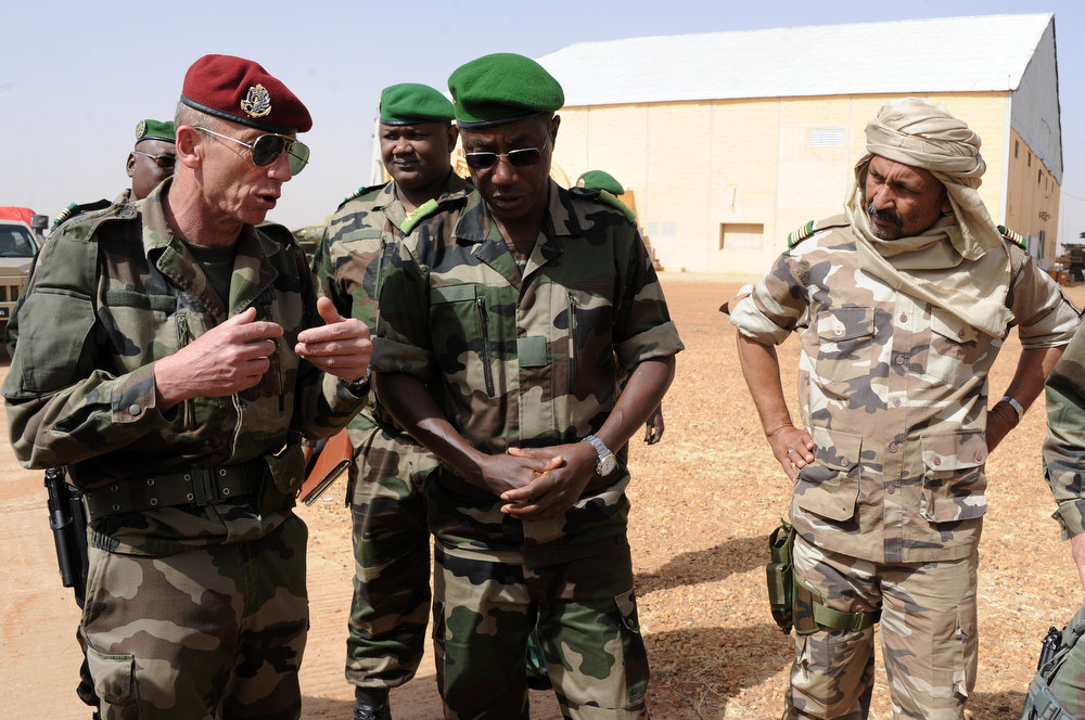 Description of . Niger army chief of staff Seini Garba (C), flanked by Mali\'s army colonel Alaji Ag Gamou (R), listens to French Colonel Zavier (L) on February 2, 2013 in Gao. French President Francois Hollande received a rapturous welcome as he visited Mali to push for African troops to take over a French-led offensive that drove back Islamist rebels from the country\'s desert north.  SIA KAMBOU/AFP/Getty Images