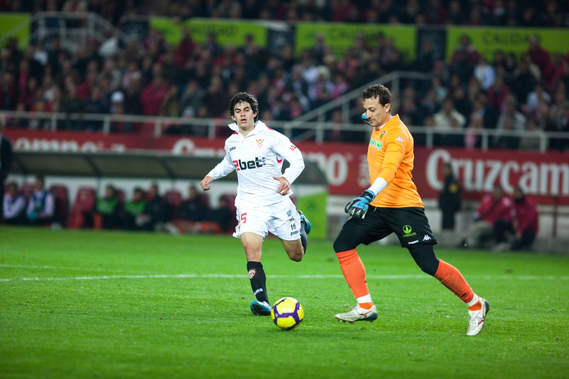Cesar, Valencia goalkeeper, tries to clear the ball before Perotti. Spanish Liga game between Sevilla FC and Valencia CF. Sanchez Pizjuan stadium, Seville, Spain, 31 January 2010
