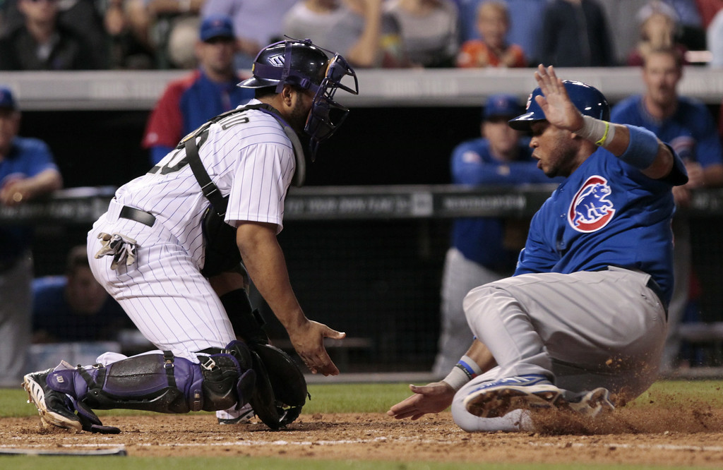 . Chicago Cubs\' Luis Valbuena, right, slides safely at home as Colorado Rockies catcher Wilin Rosario (20) waits for the throw in the seventh inning of a baseball game in Denver on Tuesday, Aug. 5, 2014.(AP Photo/Joe Mahoney)