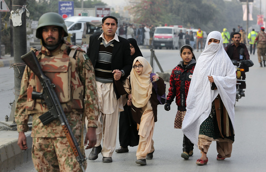 . Pakistani parents escort their children outside a school attacked by the Taliban in Peshawar, Pakistan, Tuesday, Dec. 16, 2014. Taliban gunmen stormed a military-run school in the northwestern Pakistani city of Peshawar on Tuesday, killing and wounding scores, officials said, in the highest-profile militant attack to hit the troubled region in months. (AP Photo/B.K. Bangash)