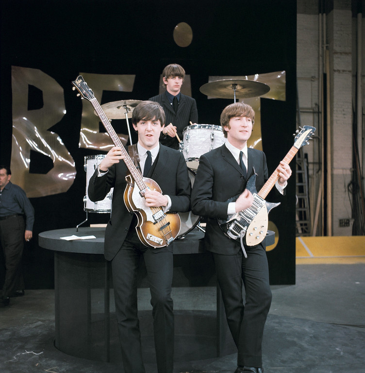". Three members of the Beatles, from left, Paul McCartney, left, John Lennon and drummer Ringo Starr are shown on the set of ""The Ed Sullivan Show"" in New York, Feb. 8, 1964.  (AP Photo)"
