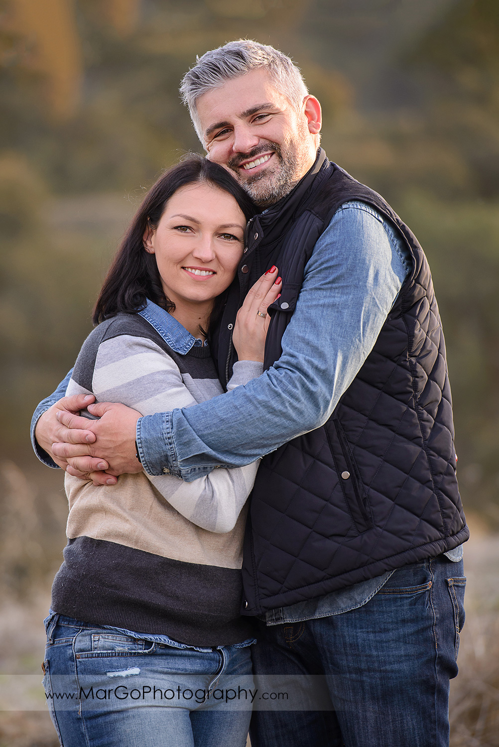 3/4 vertical portrait of man and woman wearing blue and grey clothes looking into camera during family session at Diablo Foothills Regional Park in Walnut Creek