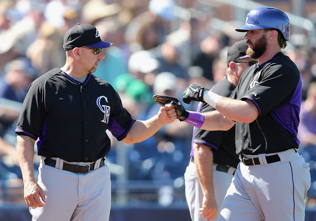. Manager Walt Weiss #22 of the Colorado Rockies high five Charlie Blackmon #19 after he scored a third inning run against the Seattle Mariners during the spring training game at Peoria Stadium on March 3, 2014 in Peoria, Arizona.  (Photo by Christian Petersen/Getty Images)