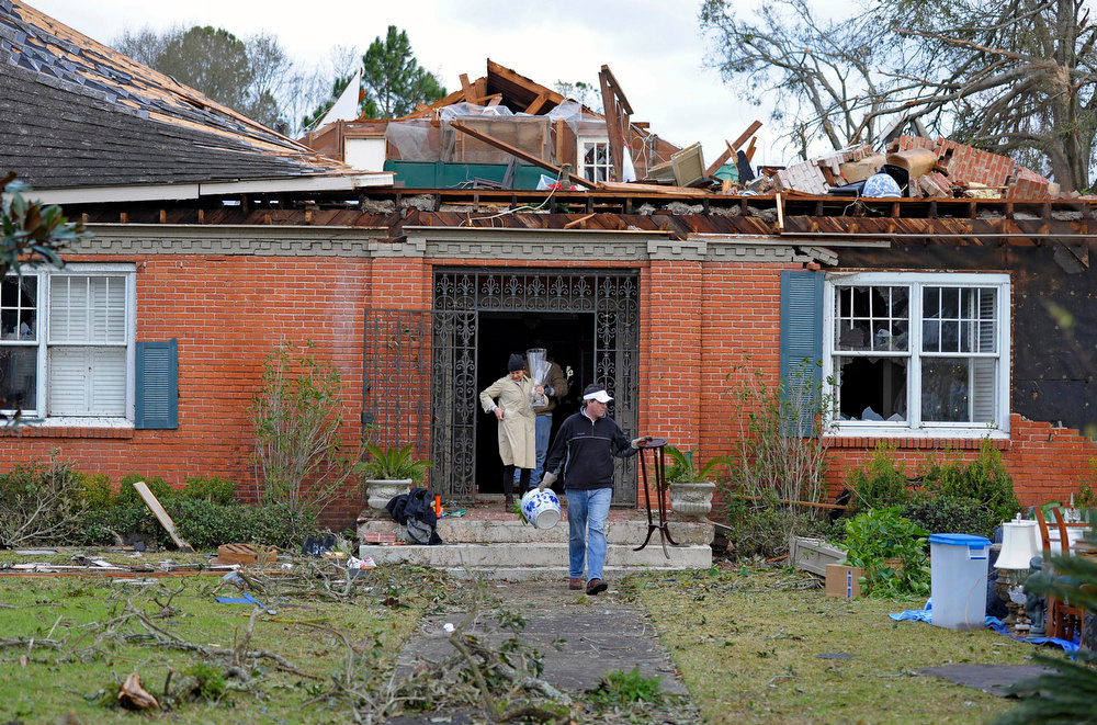 . Tim Clarke, in black jacket, carries antiques from the the damaged home of family friend Anne Zieman (not pictured) as residents clean up and assess the damage from a Christmas Day tornado Wednesday, Dec. 26, 2012  in Mobile, Ala. With only a handful of injuries and no deaths reported statewide from the storms, the head of the state\'s emergency response said it was difficult to fathom how the toll wasn\'t worse. (AP Photo/G.M. Andrews)