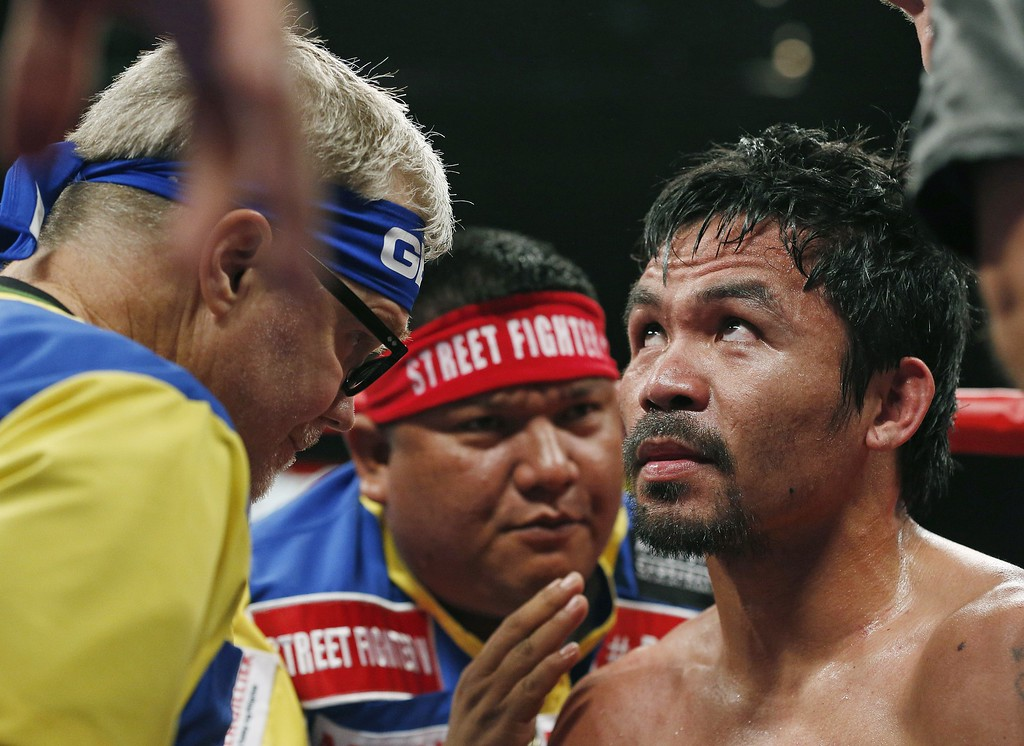 . Manny Pacquiao, from the Philippines, right, listens to his trainer Freddie Roach, left, during their welterweight title fight on Saturday, May 2, 2015 in Las Vegas. (AP Photo/John Locher)