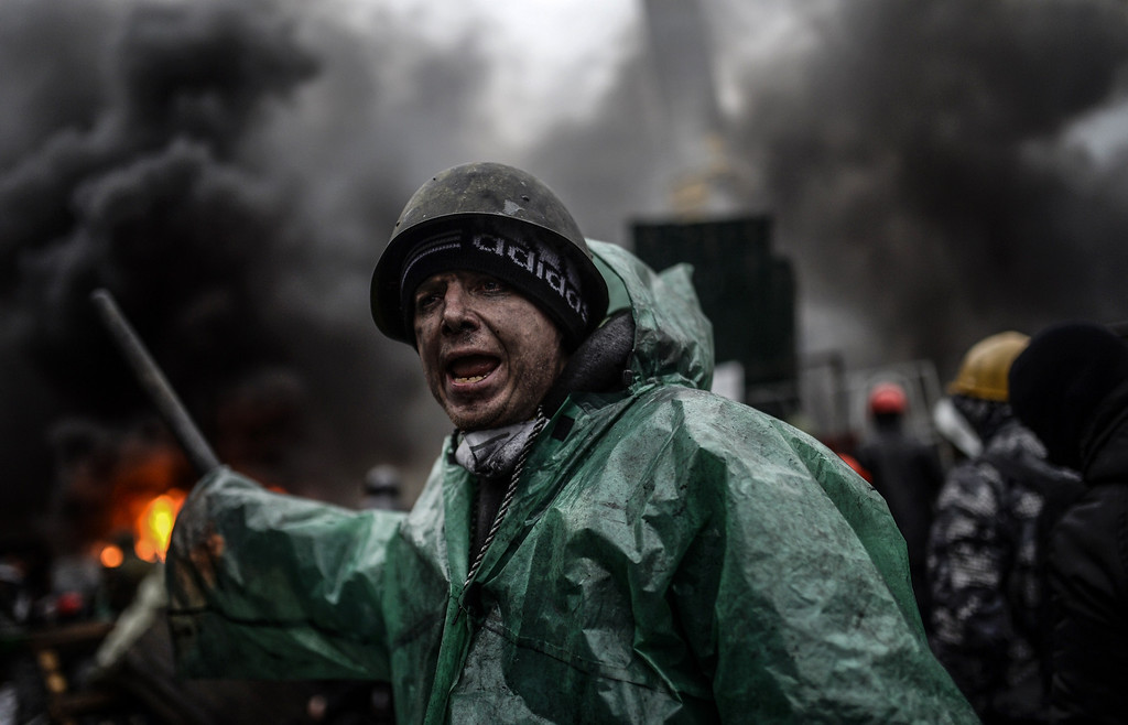 . A protester stands behind barricades during clashes with police on February 20, 2014 in Kiev. AFP PHOTO/BULENT  KILIC/AFP/Getty Images