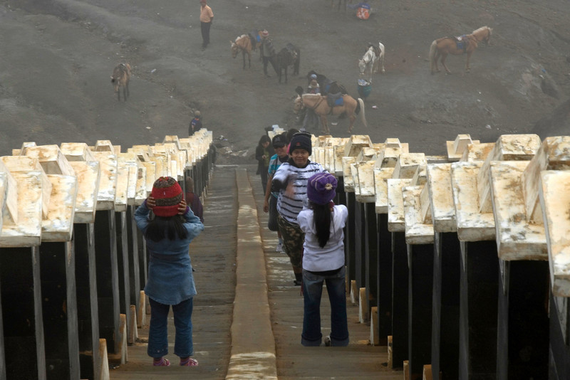 Kids walking up the stairs to Mount Bromo crater in Indonesia