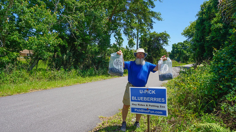 John holding bags of blueberries at the sign