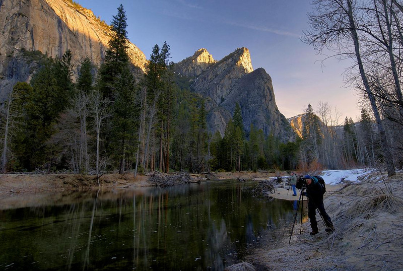 Just hours ago these crystal clear waters of the Merced River were part of the snow and ice fields of the Yosemite high country plateau. Here they reveal the river bottom's details. These peaks are called Three Brothers. February 14, 2010, 6:45 AM. Pro Photographer Tibor Vari is in the black outfit, photographing Cathedral Rock behind me.