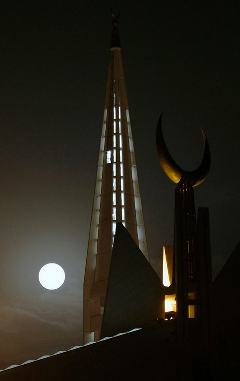 ". A perigee moon, also known as a supermoon, looks over the grand Faisal mosque in Islamabad, Pakistan,Saturday, July 12, 2014. The phenomenon, which scientists call a ""perigee moon,\"" occurs when the moon is near the horizon and appears larger and brighter than other full moons. (AP Photo/Anjum Naveed)"