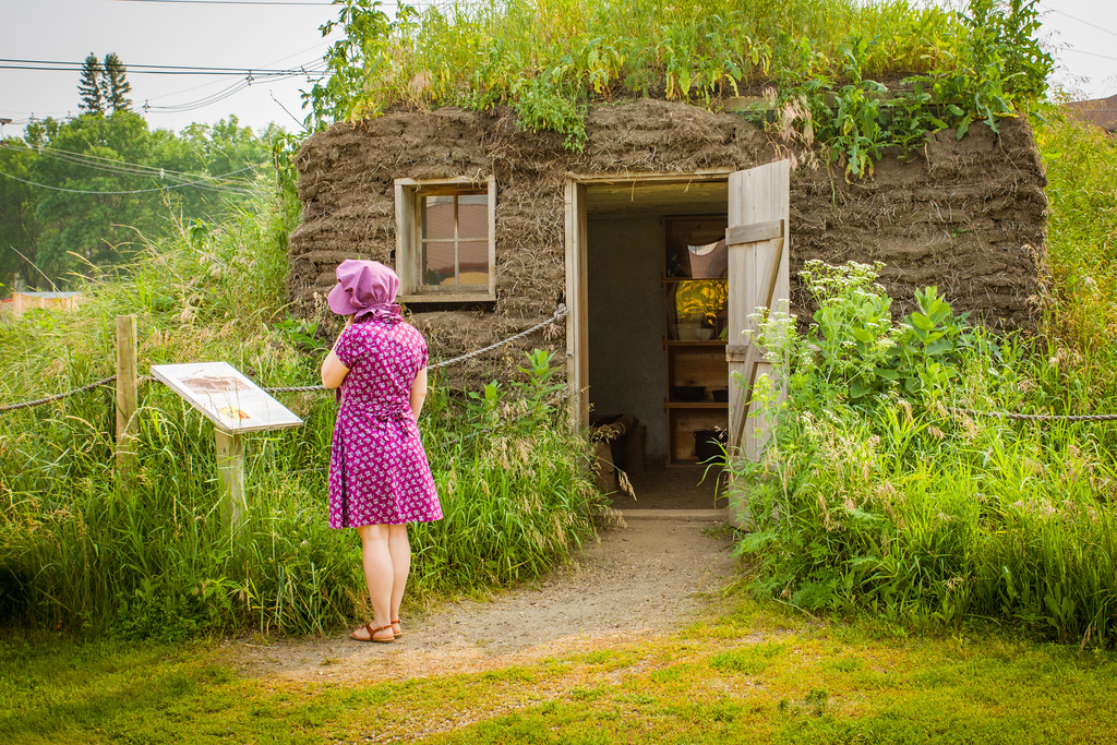 Becky, wearing her bonnet, examines an interpretive sign in front of a sod house that is covered and surrounded by tall prairie grasses.