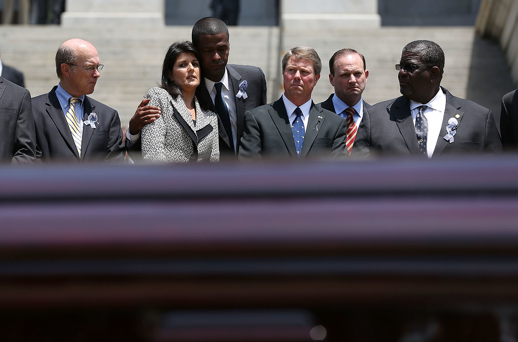 . South Carolina Governor Nikki Haley is hugged as she looks while standing with other lawmakers as South Carolina Highway Patrol Honor Guard prepare to carry the coffin of church pastor and South Carolina State Sen. Clementa Pinckney to lie in repose at the Statehouse Rotunda on June 24, 2015 in Columbia, South Carolina. Pinckney was one of nine people killed during a Bible study inside Emanuel AME church in Charleston. U.S. President Barack Obama and Vice President Joe Biden are expected to attend the funeral which is set for Friday June 26 at the TD Arena.  (Photo by Joe Raedle/Getty Images)