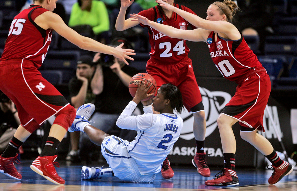 . Duke guard Alexis Jones (2) looks for help from the floor under pressure from Nebraska defenders including Rachel Theriot (24) and Jordan Hooper (35) during a regional semifinal game of the women\'s NCAA college basketball tournament Sunday, March 31, 2013, in Norfolk, Va. (AP Photo/Jason Hirschfeld)
