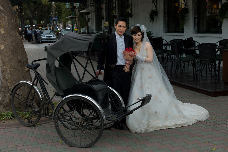 Couples take pre-wedding photos about a month in advance at picturesque locations in Vietnam, here in front of the Sofitel Metropole hotel in Hanoi, with a fancy cyclo (used to transport people around town).