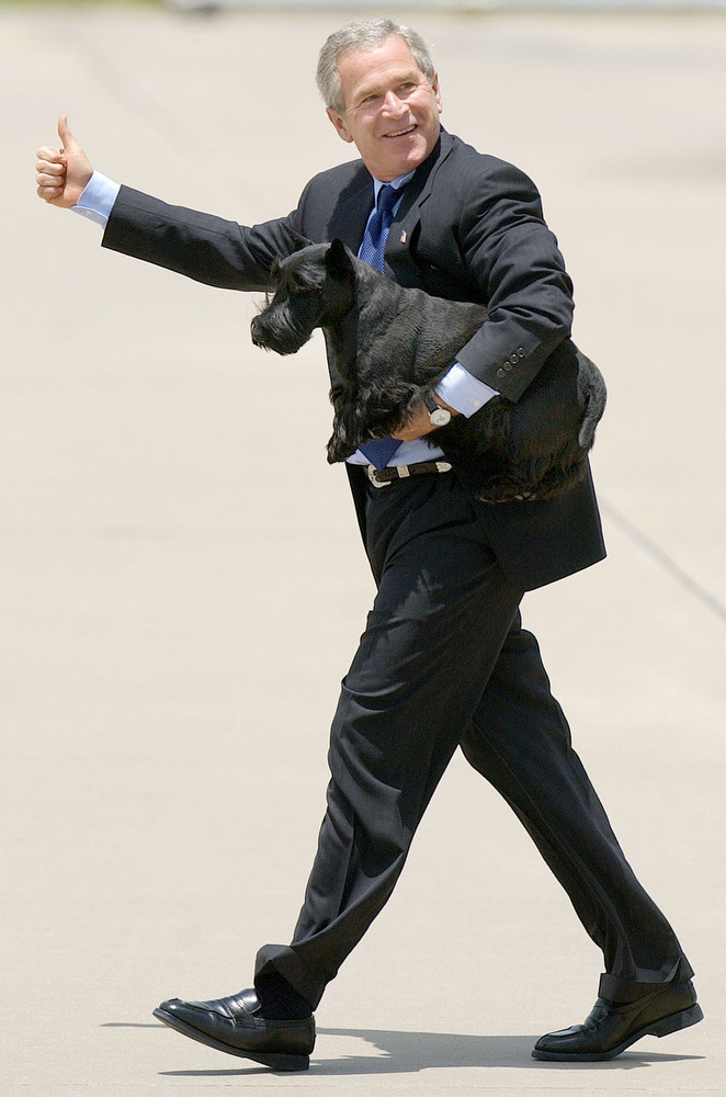Description of . President Bush, carrying his dog Barney, gives a thumbs-up after arriving at TSTC Airfield Friday, July 23, 2004, in Waco, Texas. Bush will spend a week at his nearby Crawford, Texas, ranch. (AP Photo/Duane A. Laverty)
