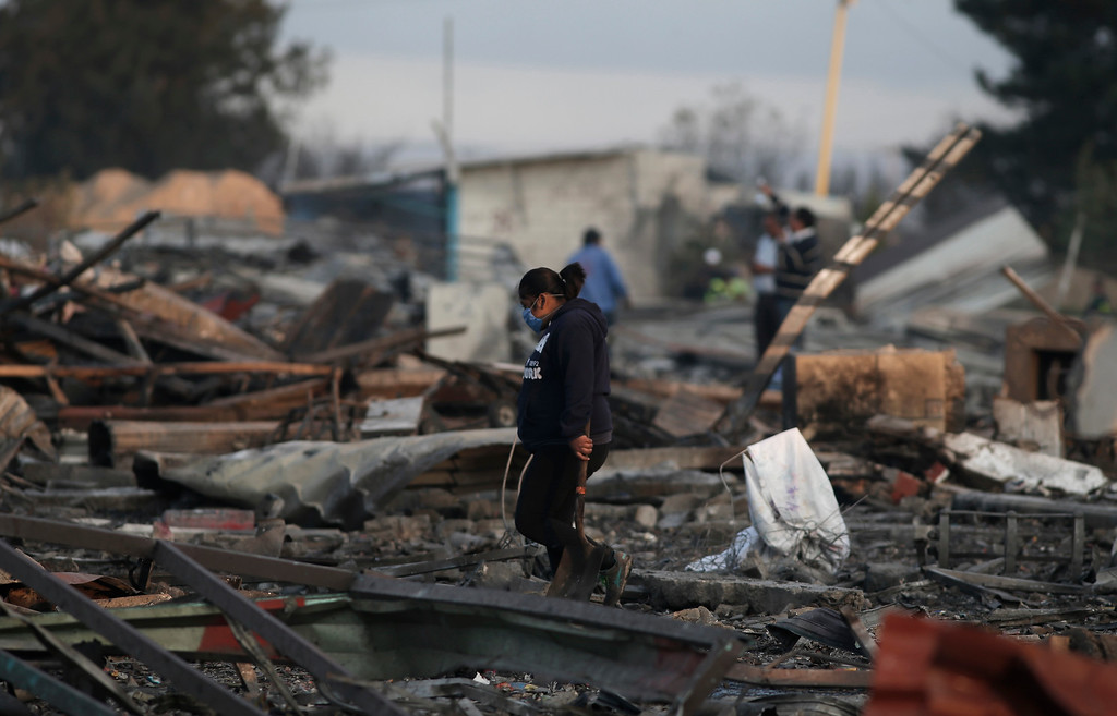 . A woman carries a shovel as she walks through the scorched ground of the open-air San Pablito fireworks market, in Tultepec, outskirts of Mexico City, Mexico, Tuesday, Dec. 20, 2016.  An explosion ripped through Mexico�s best-known fireworks market on the northern outskirts of the capital Tuesday, injuring scores and killing dozens, according to Mexican Federal Police. (AP Photo/Eduardo Verdugo)