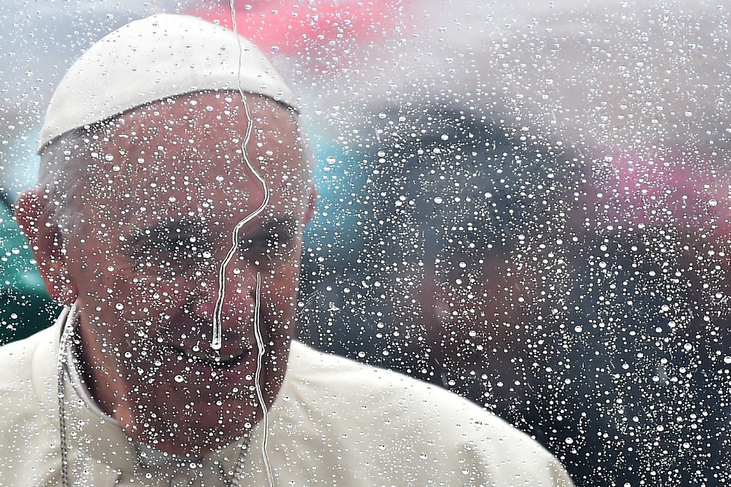 . Pope Francis is seen through a glass covered by rainwater on May 14, 2016 in St Peter\'s Square at the Vatican for a Jubilee Audience.   / AFP PHOTO / GABRIEL  BOUYS/AFP/Getty Images