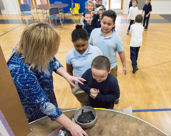03/27/18 Wesley Bunnell | Staff First grade student Jayden Burgos smiles as he waits for his chance to play with the magnetic slime with assistance from his teacher Mrs. Poff at the 2nd Annual Smalley Academy Science Fair on Tuesday morning featuring science exhibits by all grades.