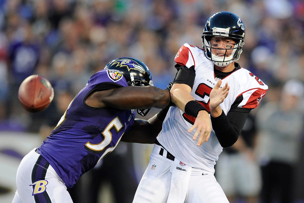 . Atlanta Falcons quarterback Matt Ryan releases a low pass under pressure from Baltimore Ravens linebacker Elvis Dumervil during the first half of a preseason NFL football game in Baltimore, Thursday Aug. 15, 2013. (AP Photo/Nick Wass)