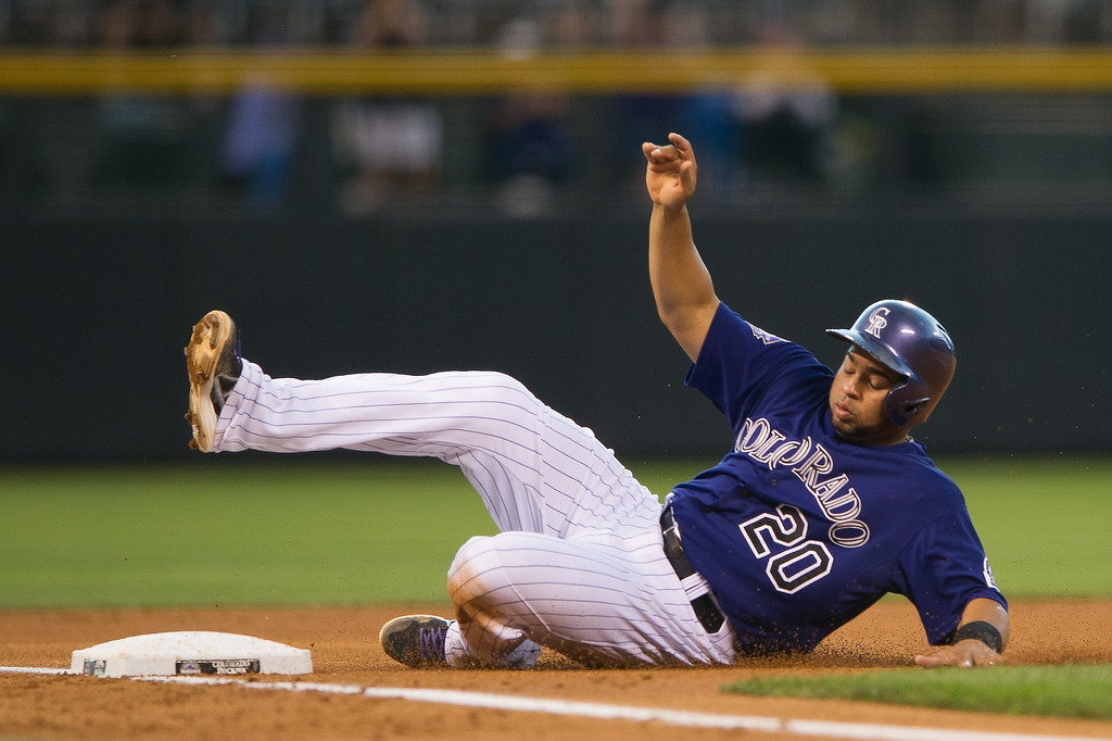 . Wilin Rosario #20 of the Colorado Rockies slides safely into third base, advancing on a fielding error during a game against the San Diego Padres at Coors Field on August 12, 2013 in Denver, Colorado. The Rockies led the Padres 2-0 after one inning.  (Photo by Dustin Bradford/Getty Images)