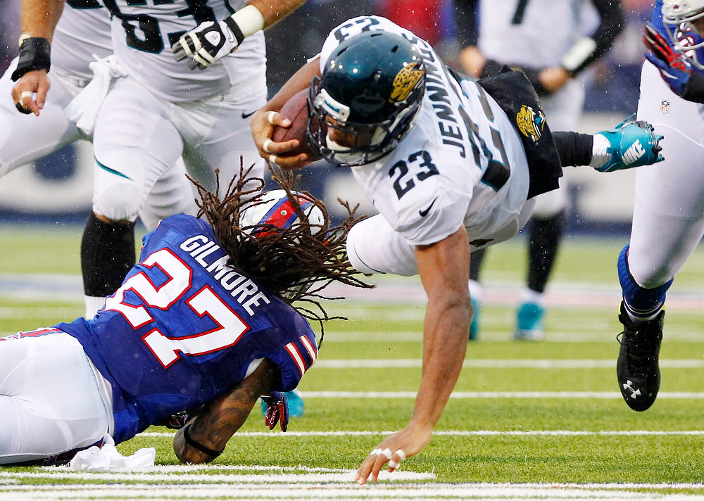 . Jacksonville Jaguars\' Rashad Jennings (23) dives over Buffalo Bills cornerback Stephon Gilmore (27) for extra yards during the first half of an NFL football game Sunday, Dec. 2, 2012 in Orchard Park, N.Y. Jennings was  hurt on the play. (AP Photo/Bill Wippert)