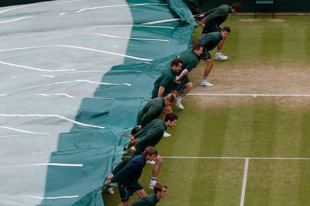 . Ground staff pulls the covers onto Court One as rain halts play between Sloane Stephens of the United States and Marion Bartoli of France in a Women\'s singles quarterfinal match at the All England Lawn Tennis Championships in Wimbledon, London, Tuesday, July 2, 2013. (AP Photo/Anja Niedringhaus)