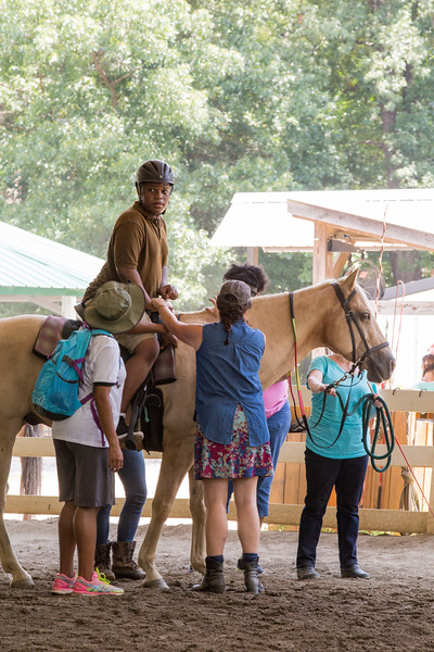 Cameron Scott, 14, visiting with the special needs camp Camp Best Friends, gets on horseback with help.  Chastain Horse Park provides therapeutic programs for special needs campers and for those in need of physical and occupational therapies.  The program is comprised of professional therapist, equestrians and volunteers.    (Jenni Girtman / Atlanta Event Photography)