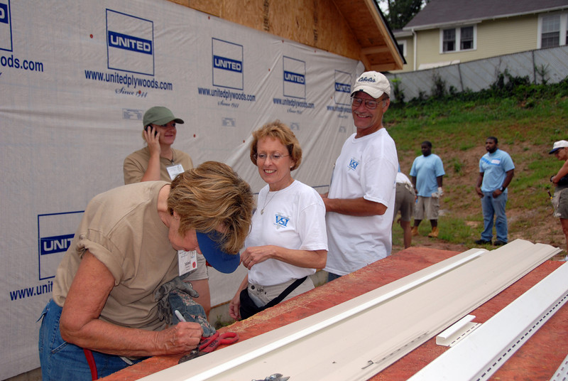 """Mimi volunteers to be a vinyl siding """"cutter"""" as Jery Huntley from Vinyl Siding Institute stands by to assist. mlj"""