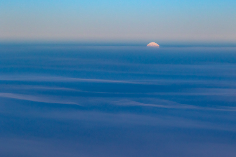 And aerial photo of the moon starting to rise above wispy blue clouds