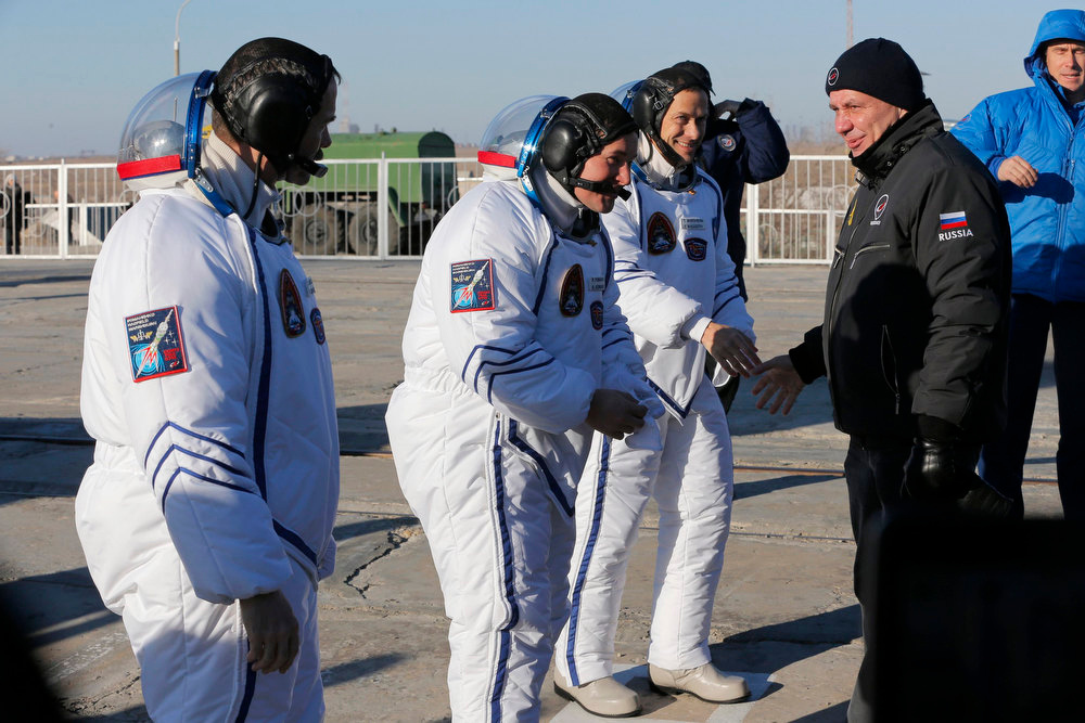 . Russia\'s Roskosmos space agency chief Vladimir Popovkin (R) greets members of the International Space Station (ISS) crew U.S. astronaut Thomas Marshburn (2nd R), Russian cosmonaut Roman Romanenko (2nd L) and Canadian astronaut Chris Hadfield before they board the Soyuz TMA-06M spacecraft at the Baikonur cosmodrome December 19, 2012.  REUTERS/Dmitry Lovetsky/Pool