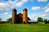 Old silos in the middle of a large grassy meadow.
