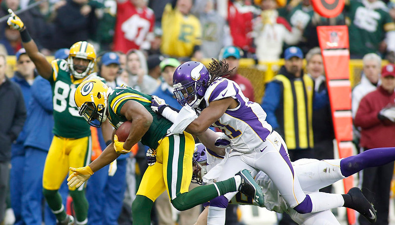 . Green Bay Packers wide receiver Randall Cobb (C) gets a first down against the Minnesota Vikings safety Mistral Raymond during the second half of their NFL football game in Green Bay, Wisconsin December 2, 2012.   REUTERS/Darren Hauck
