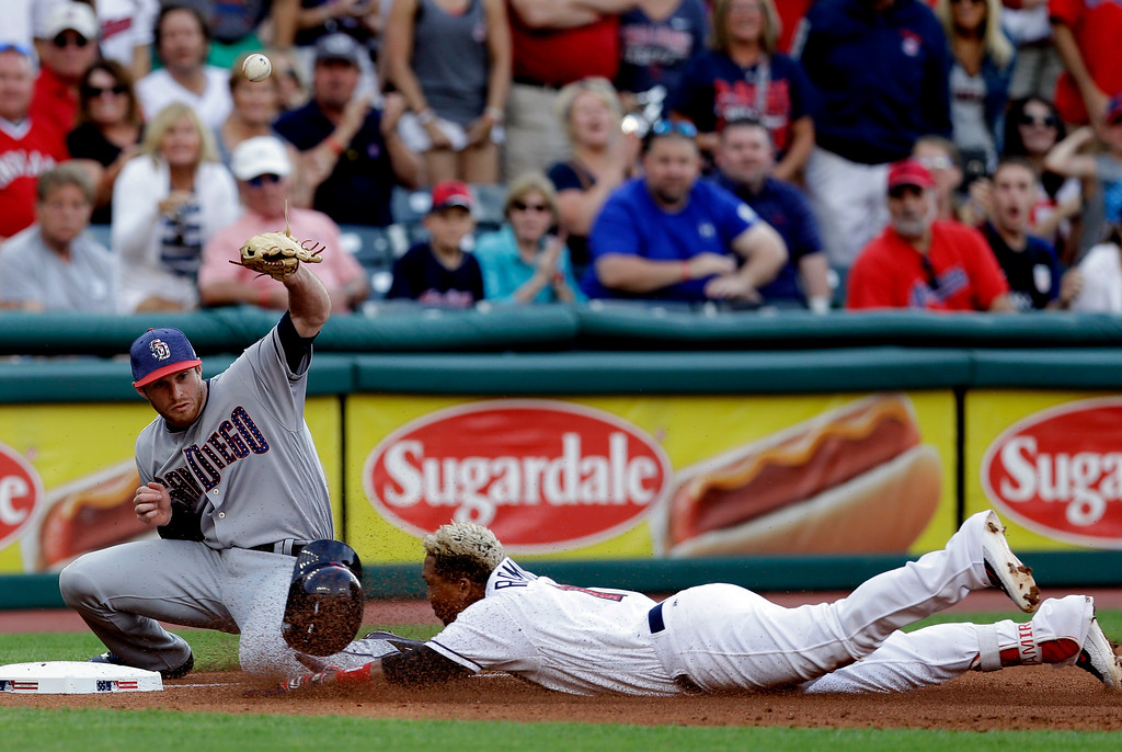 . San Diego Padres third baseman Cory Spangenberg can\'t handle the ball as Cleveland Indians\' Jose Ramirez slides into third base for a triple in the second inning of a baseball game, Tuesday, July 4, 2017, in Cleveland. (AP Photo/Tony Dejak)