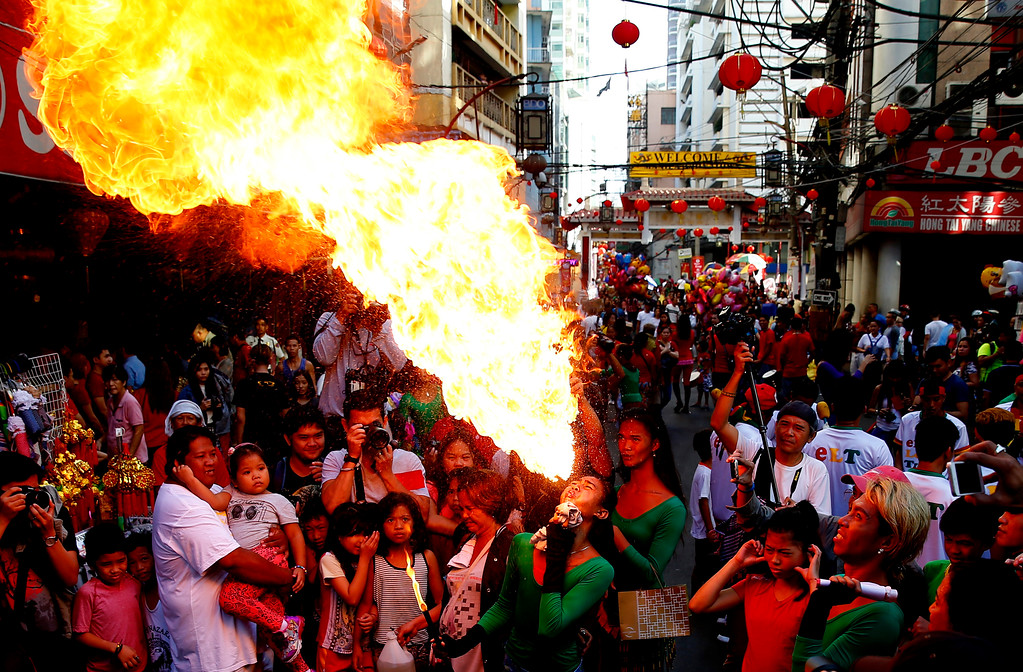 . A fire-eater performs on the street in celebration of the Chinese Lunar New Year Friday, Feb. 16, 2018 at Manila\'s Chinatown district, Philippines. (AP Photo/Bullit Marquez)