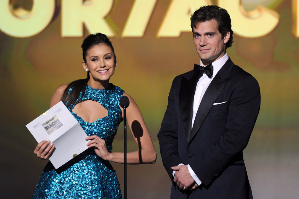 Description of . Presenters Nina Dobrev (L) and Henry Cavill speak onstage at the 18th Annual Critics' Choice Movie Awards held at Barker Hangar on January 10, 2013 in Santa Monica, California.  (Photo by Kevin Winter/Getty Images)