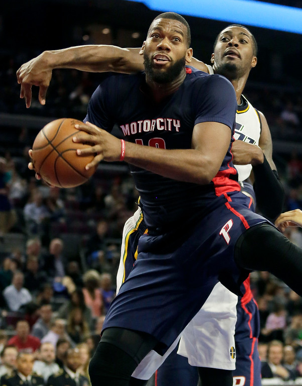 . Detroit Pistons\' Greg Monroe, left, grabs a rebound in front of Utah Jazz\'s Derrick Favors during the second half of an NBA basketball game Sunday, Nov. 9, 2014, in Auburn Hills, Mich. The Jazz defeated the Pistons 97-96. (AP Photo/Duane Burleson)