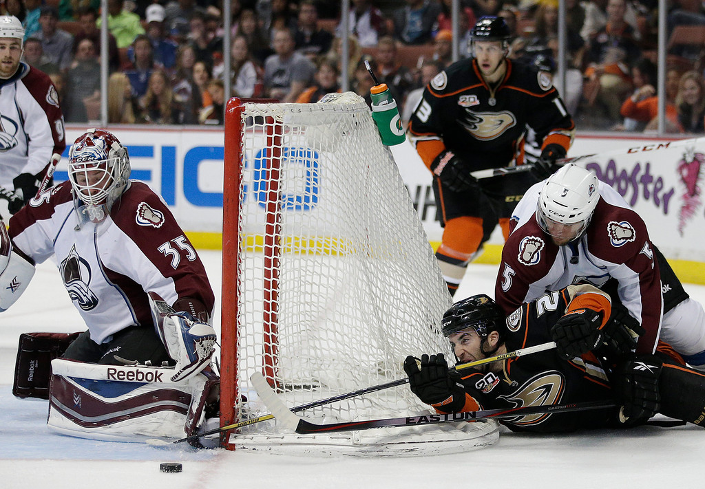 . Anaheim Ducks\' Kyle Palmieri (21) is defended by Colorado Avalanche\'s Nate Guenin(5) as he tries to score against Colorado Avalanche goalie Jean-Sebastien Giguere(35) during the second period of an NHL hockey game on Sunday, April 13, 2014, in Anaheim, Calif. (AP Photo/Jae C. Hong)