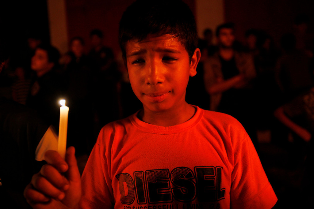 . A Palestinian youth holds a light candle at the site where Hamas\' military commander Ahmad Jabari was killed a year ago in an Israeli air strike during their battle, as he and others commemorate the anniversary of his death and the battle in Gaza City, Thursday, Nov. 14, 2013. (AP Photo/Adel Hana)