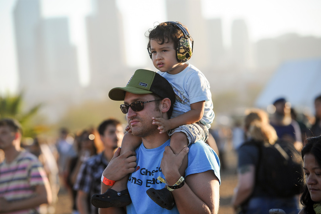 . Adam Lovinus watches a set with his son Jah Lovinus, 2, who wears ear muffs at the FYF Fest in downtown L.A., Saturday, August 24, 2013. (Michael Owen Baker/L.A. Daily News)