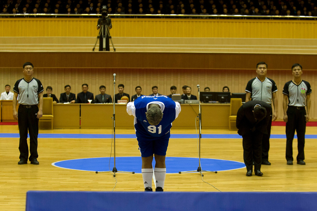 . Dennis Rodman bows to North Korean leader Kim Jong Un, seated above in the stands, before an exhibition basketball game with U.S. and North Korean players at an indoor stadium in Pyongyang, North Korea on Wednesday, Jan. 8, 2014. (AP Photo/Kim Kwang Hyon)