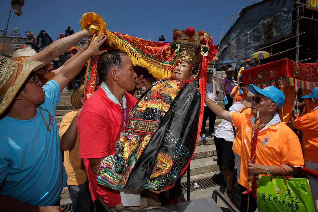 . Villagers carry a statue of a Chinese god during a parade on the outlying Cheung Chau island in Hong Kong to celebrate the Bun Festival Tuesday, May 22, 2018. Bun Festival, the Taoist God of the Sea, is worshipped and evil spirits are scared away by loud gongs and drums during the procession. The celebration includes bun scrambling, parades, opera performances, and children dressed in colorful costumes. (AP Photo/Kin Cheung)