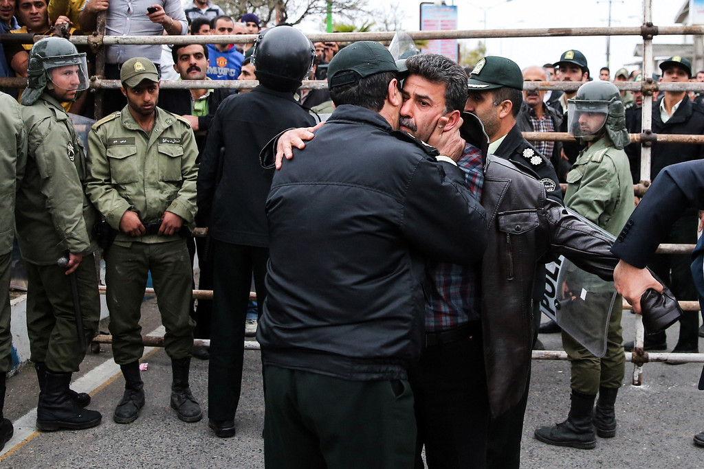 . A police office kisses Abdolghani Hosseinzadeh (C-R) the father of Abdolah Hosseinzadeh who was killed by a fellow Iranian, named Balal, in a street fight with a knife in 2007, during Balal\'s execution ceremony in the northern city of Nowshahr on April 15, 2014.  AFP PHOTO/ARASH KHAMOOSHI/AFP/Getty Images