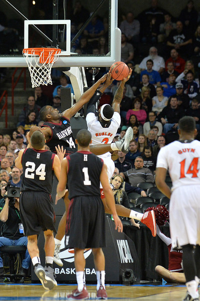 March 20, 2014: Harvard Crimson forward Steve Moundou-Missi (14) contests a shot from Cincinnati Bearcats forward Titus Rubles (2) during a second round game of the NCAA Division I Men's Basketball Championship between the 5-seed Cincinnati Bearcats and the 12-seed Harvard Crimson at Spokane Arena in Spokane, Wash. Harvard defeated Cincinnati 61-57.