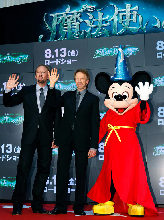 ". Actor Nicolas Cage, left, and producer Jerry Bruckheimer, center, pose for photographers along side Mickey Mouse during the Japan premiere of their latest movie ""The Sorcerer\'s Apprentice\"" in Tokyo, Wednesday, July 21, 2010. (AP Photo/Shizuo Kambayashi)"