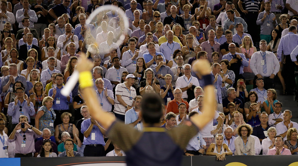 . The crowd applauds as Serbia\'s Novak Djokovic celebrates after defeating Spain\'s David Ferrer in their semifinal match at the Australian Open tennis championship in Melbourne, Australia, Thursday, Jan. 24, 2013. (AP Photo/Andy Wong)