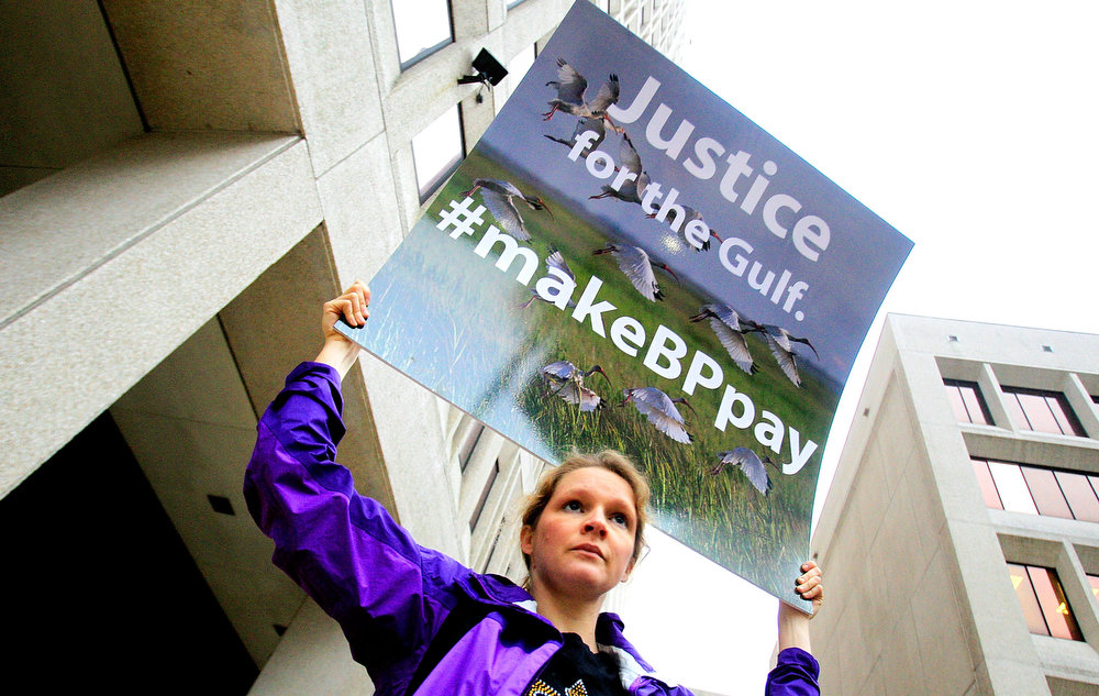 Description of . An activist holds a sign during a protest in front of the Hale Boggs Federal Building on the first day of the trial over the Deep Water Horizon oil rig spill on February 25, 2013 in New Orleans, Louisiana. 11 men were killed during the accident and over 4 million barrels of oil spilled into the Gulf of Mexico in 2010. (Photo by Sean Gardner/Getty Images)